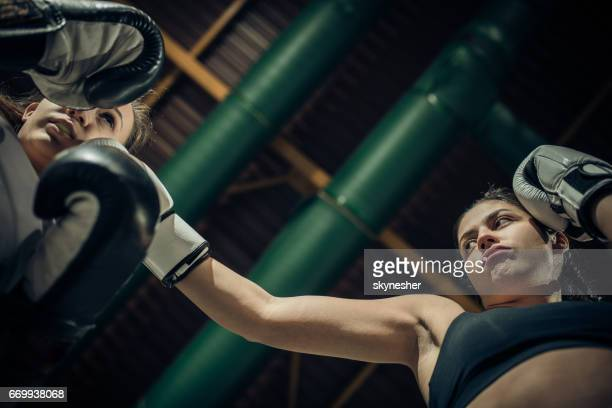 Below view of a female boxers during a fight in a gym.