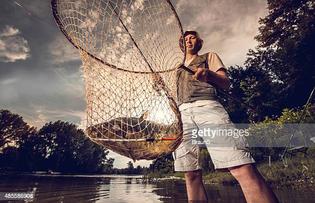 Below view of a fisherman holding his catch in net.