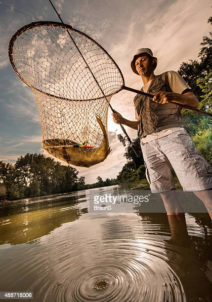 Below view of a fisherman holding his fish in net.