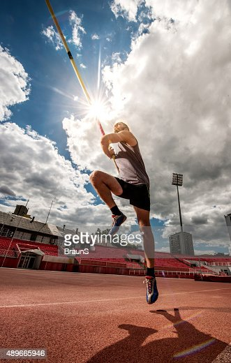 Below view of a man during a pole vault competition.