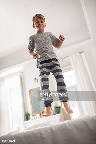 Debajo de vista de un pequeño niño saltar en una cama.