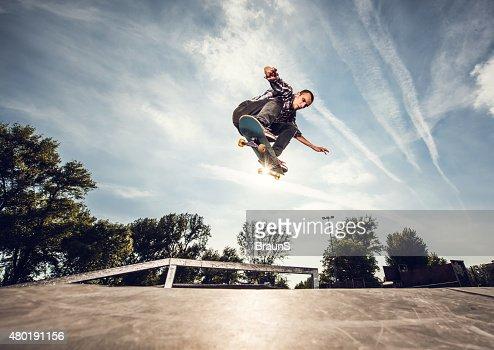 Below view of a street skateboarder in Ollie position.