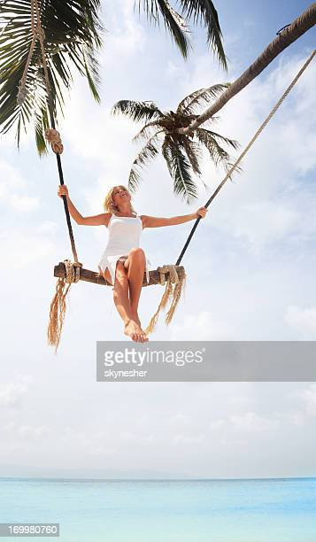 Below view of a woman swinging on the tree swing.