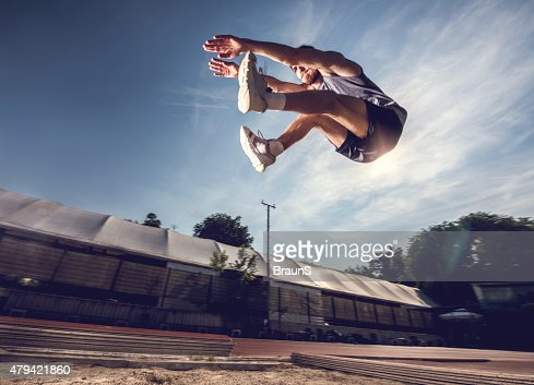 Below view of a young athlete in a long jump.