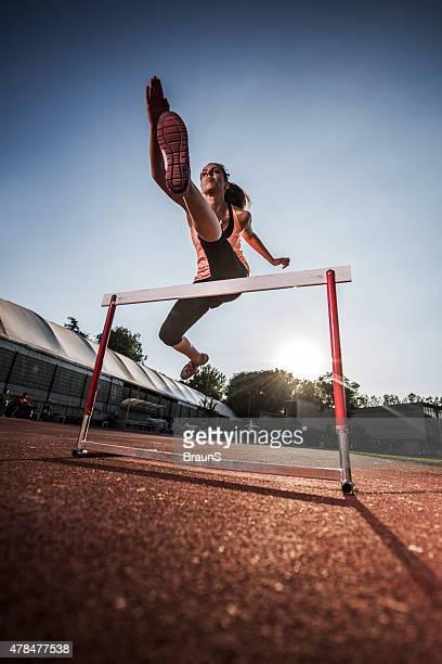 Below view of a young woman jumping hurdle.