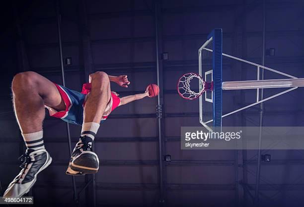 Abaixo de vista de Jogador de basquete colocando bola em arco.