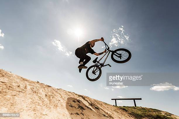 Below view of bmx cyclist jumping against the sky.