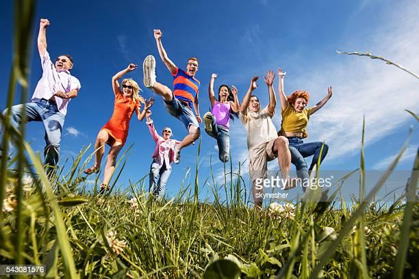 A continuación vista de Alegre personas Saltar al aire libre con alzar los brazos.