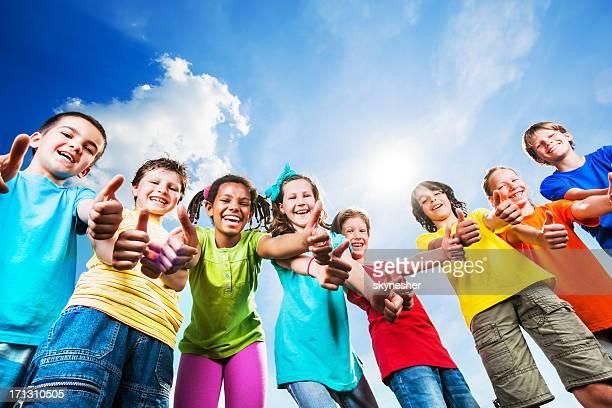 Below view of children showing ok sign.