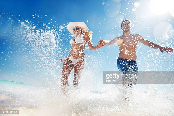 Below view of couple having fun while running through sea.