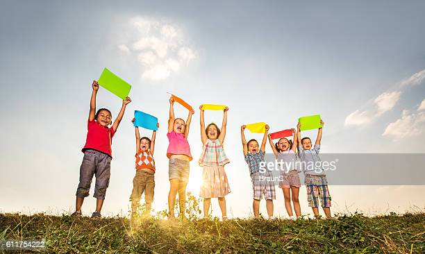 Below view of cute children holding multi-colored papers in meadow.