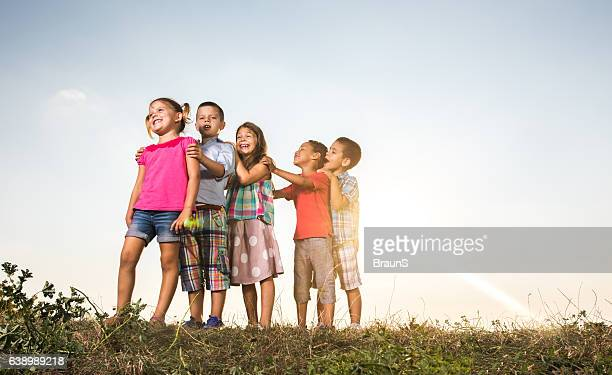 Below view of cute kids standing in a row outdoors.