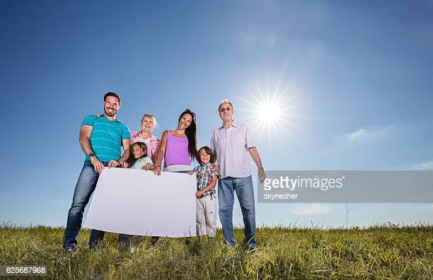 Below view of extended family in meadow holding empty banner.