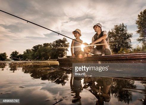 Abaixo vista de pai e filho de pesca ao pôr do sol.
