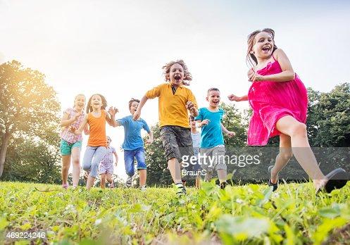 Below view of happy children running in the park.