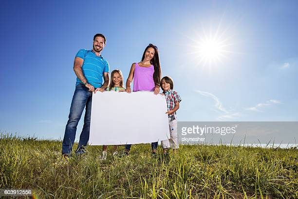 Below view of happy family holding blank placard in nature.