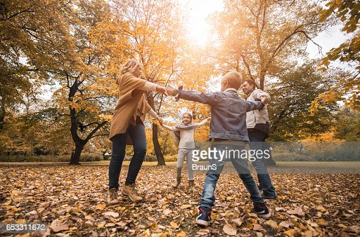 Below view of happy family playing ring-around-the-rosy in nature. : Stock-Foto