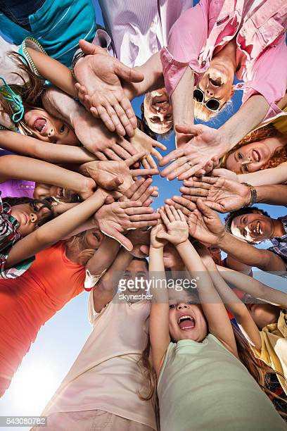 Below view of happy people joining their hands in unity.
