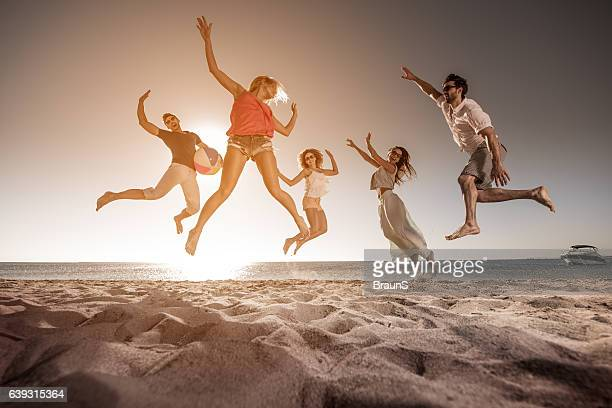 Below view of happy people jumping on the beach.