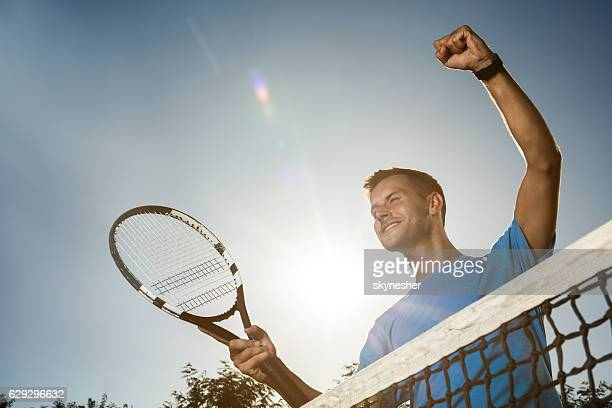 Below view of happy tennis player celebrating against the sky.