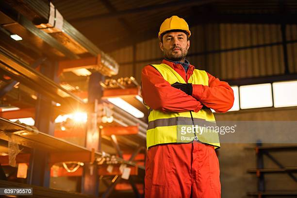 Below view of metal worker with crossed arms in warehouse.