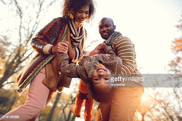 Below view of playful African American family in autumn park.