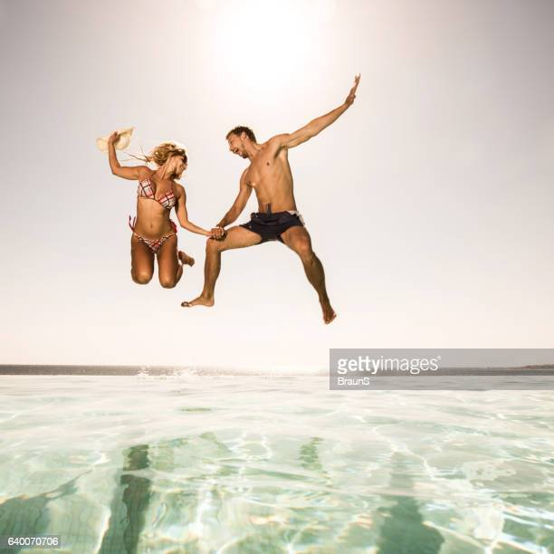 Below view of playful couple jumping into the pool.