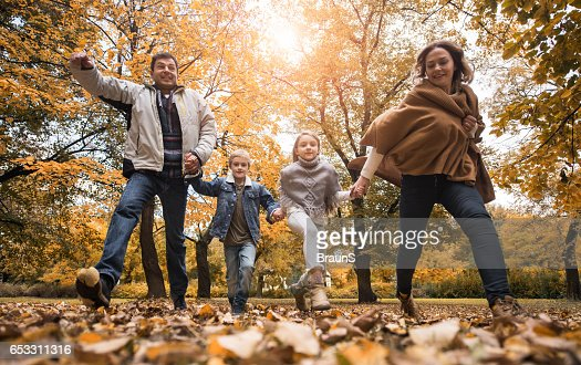 Below view of playful family during autumn day. : Photo