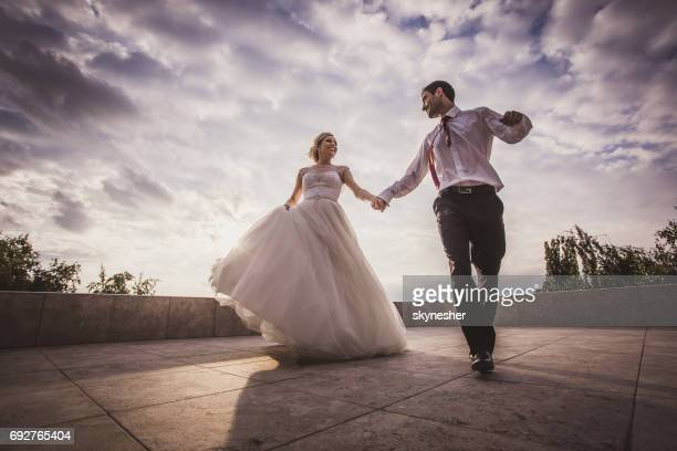 Below view of playful newlyweds having fun while holding hands and running.