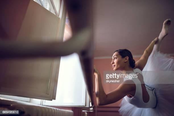 Sous vue de ballerine professionnelle qui s'étend dans le studio de danse.