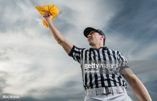 Below view of referee showing penalty against the sky.