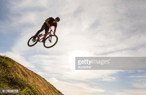 Below view of skillful cyclist jumping high up against sky.