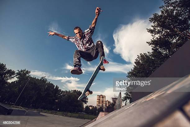 Abaixo vista de skater skillful divertir-se no Parque de skate.