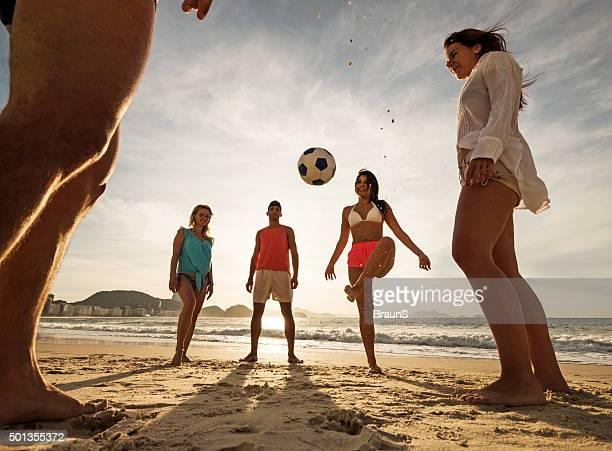 Unter Ansicht von lächelnden Freunde Fußball spielen am Strand.
