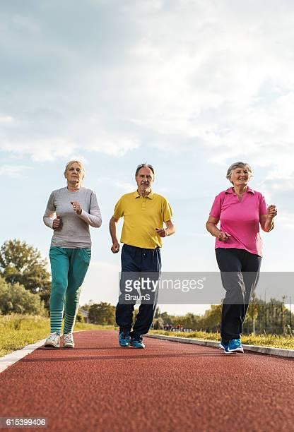 Below view of smiling senior people jogging on running track.