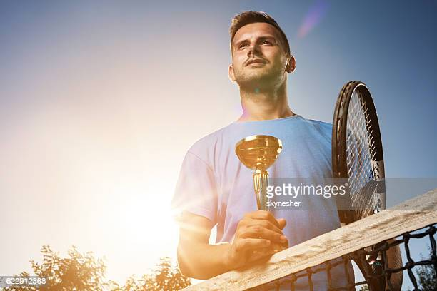 Below view of successful tennis player with winning trophy.