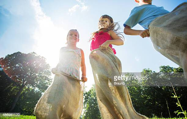 Below view of three happy kids on sack race outdoors.