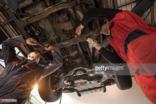Below view of two mechanics repairing a car.