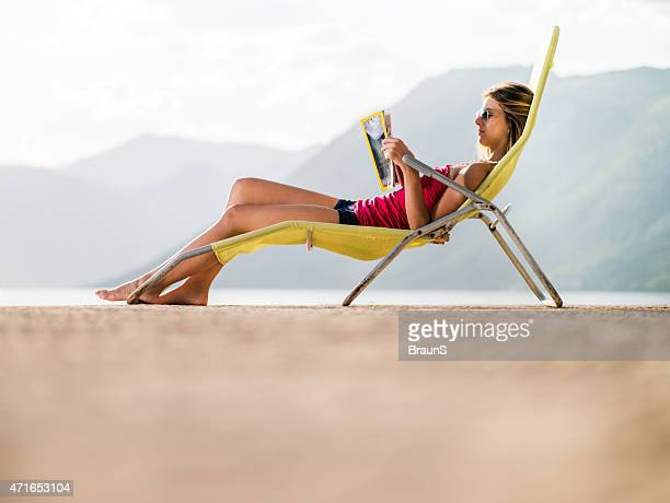 Below view of woman reading a magazine in deck chair.