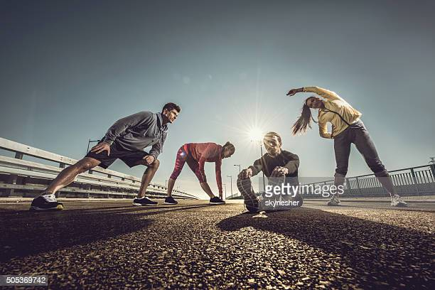 Below view of young athletes doing stretching exercises on road.