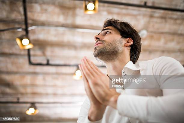 Below view of young businessman praying for something.