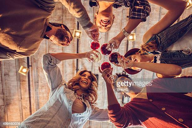 Below view of young happy friends toasting with wine.