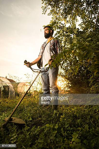 Below view of young man mowing the lawn at sunset.