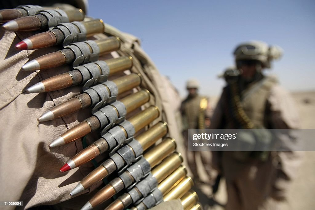Belts of .50-caliber ammunition hung from the shoulders of Marines at live-fire range near Camp Fallujah, June 13. Marines from Headquarters Company, Regimental Combat Team 5 refreshed skills on their mounted machine guns.