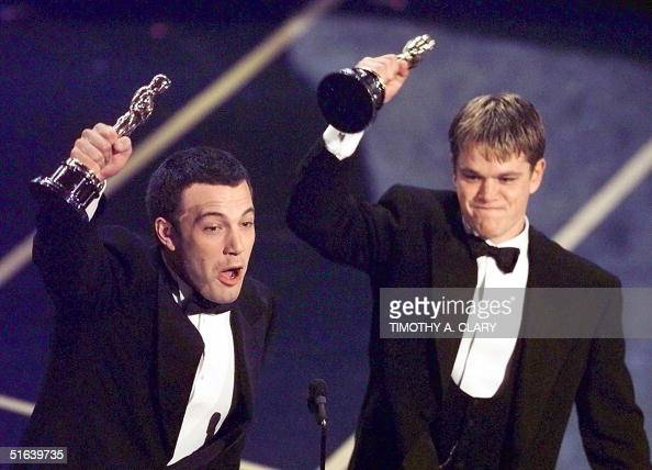 Ben Affleck and Matt Damon hold up their Oscars after winning in the Original Screenplay Category during the 70th Academy Awards at the Shrine...
