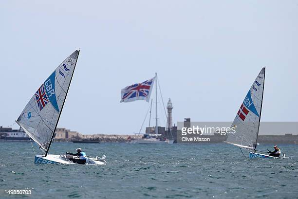 Ben Ainslie of Great Britain and Jonas HoghChristensen of Denmark compete in the Men's Finn Sailing Medal Race on Day 9 of the London 2012 Olympic...