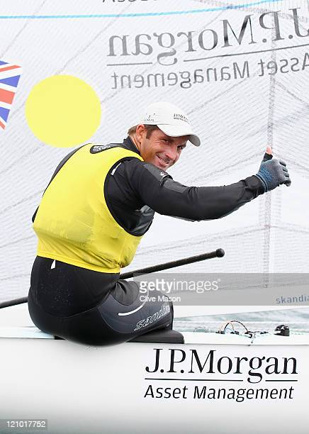 Ben Ainslie of Great Britain celebrates his gold medal with his friends dog aboard after the Finn Class medal race on day twelve of the Weymouth and...