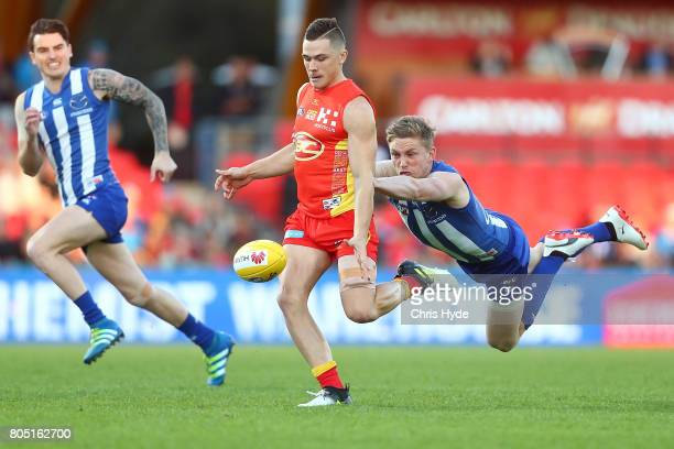 Ben Ainsworth of the Suns is tackled by Jack Ziebell of the Kangaroos during the round 15 the Gold Coast Suns and the North Melbourne Kangaroos at...