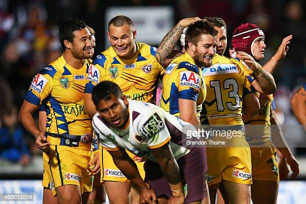 Ben Barba of the Broncos shows signs of dejection while Brett Stewart of the Sea Eagles celebrates with team mates after scoring a try during the...