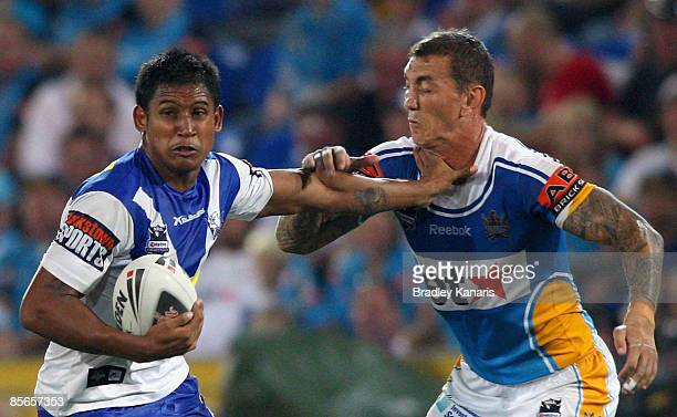 Ben Barba of the Bulldogs attempts to break free from the defence of Mat Rogers of the Titans during the round three NRL match between the Gold Coast...